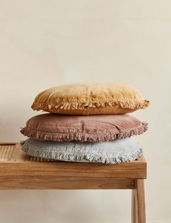 Round Fringed Velvet Cushion - pile of cushions